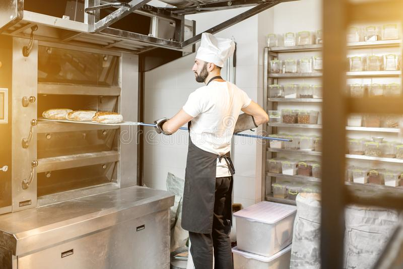 Baker που βγάζει τα ψωμιά από το φούρνο στοκ φωτογραφία