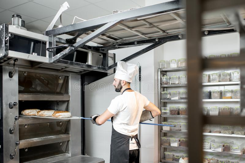Baker που βγάζει τα ψωμιά από το φούρνο στοκ φωτογραφία με δικαίωμα ελεύθερης χρήσης