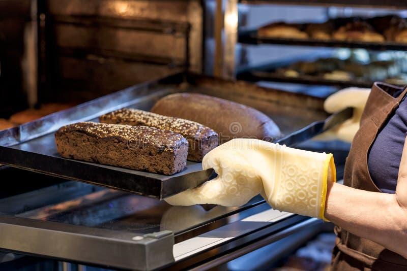 Baker που κρατά έναν δίσκο με το φρέσκο ψωμί που παίρνει το από το φούρνο στοκ εικόνες