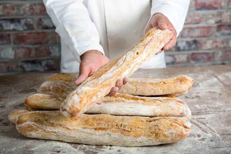 Baker που κρατά τα παραδοσιακά γαλλικά baguettes ψωμιού στοκ εικόνες