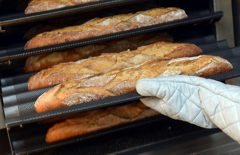 Baker που παίρνει μια φραντζόλα του πρόσφατα ψημένου ψωμιού στοκ φωτογραφίες