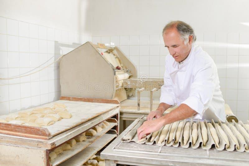 Baker που προετοιμάζει τα baguettes για το φούρνο στοκ εικόνες