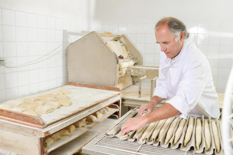 Baker που προετοιμάζει τα baguettes για το φούρνο στοκ φωτογραφία με δικαίωμα ελεύθερης χρήσης
