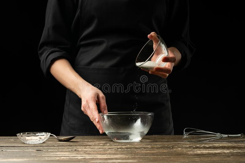 Baker που προετοιμάζει τη ζύμη ζύμης, σε ένα σκοτεινό υπόβαθρο Έννοια αρτοποιείων και προετοιμασία ζύμης στοκ φωτογραφία με δικαίωμα ελεύθερης χρήσης