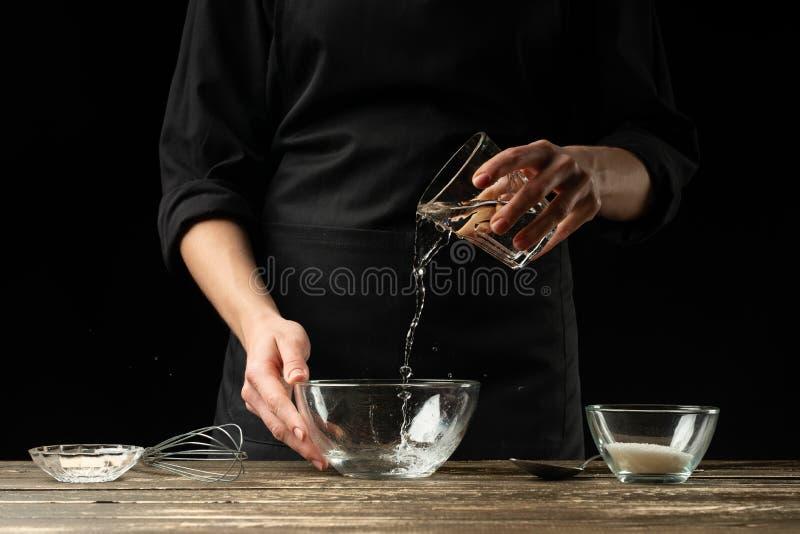 Baker που προετοιμάζει τη ζύμη ζύμης, σε ένα σκοτεινό υπόβαθρο Έννοια αρτοποιείων και προετοιμασία ζύμης στοκ φωτογραφίες
