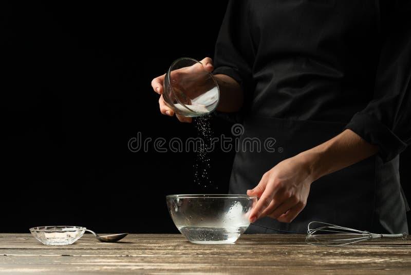 Baker που προετοιμάζει τη ζύμη ζύμης, σε ένα σκοτεινό υπόβαθρο Έννοια αρτοποιείων και προετοιμασία ζύμης στοκ εικόνες