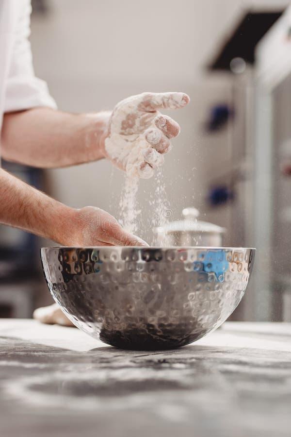 Baker προσθέτει το αλεύρι στη ζύμη σε ένα κύπελλο σιδήρου στον πίνακα στο αρτοποιείο στοκ φωτογραφίες
