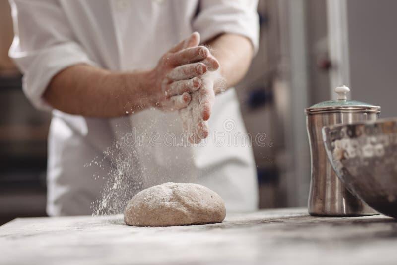 Baker προσθέτει το αλεύρι στη ζύμη στον πίνακα στο αρτοποιείο στοκ φωτογραφίες