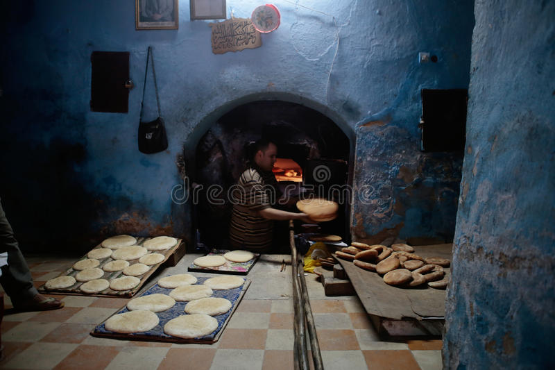 Baker baking bread pieces in ancient Medina of Fez in Morocco. A baker slides the bread into an antique wood oven in a local bakery in the city of Fez in Morocco stock photography