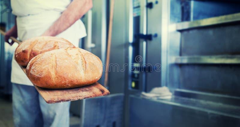 Baker in bakkerij met brood op schop royalty-vrije stock afbeeldingen