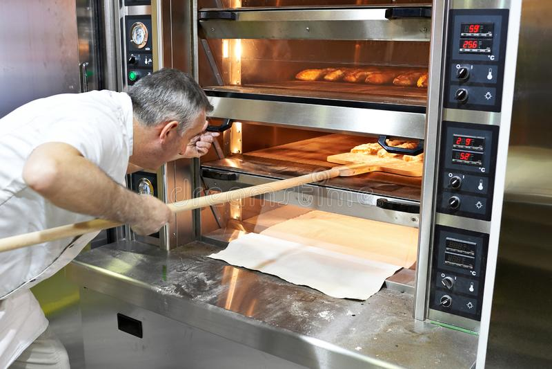 Baker bakt brood in oven stock afbeelding