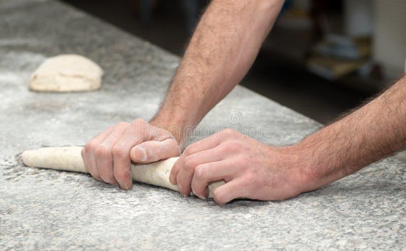Baker bereidt brooddeeg voor, sluit omhoog op zijn handen royalty-vrije stock afbeelding