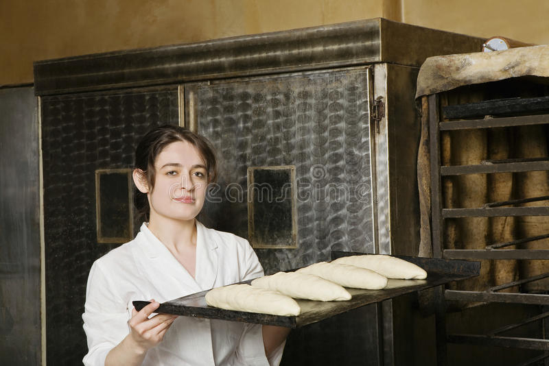 Baker Carrying Loaves Of Bread Bough To Bake. Portrait of female baker carrying loaves of bread bough to bake stock photos