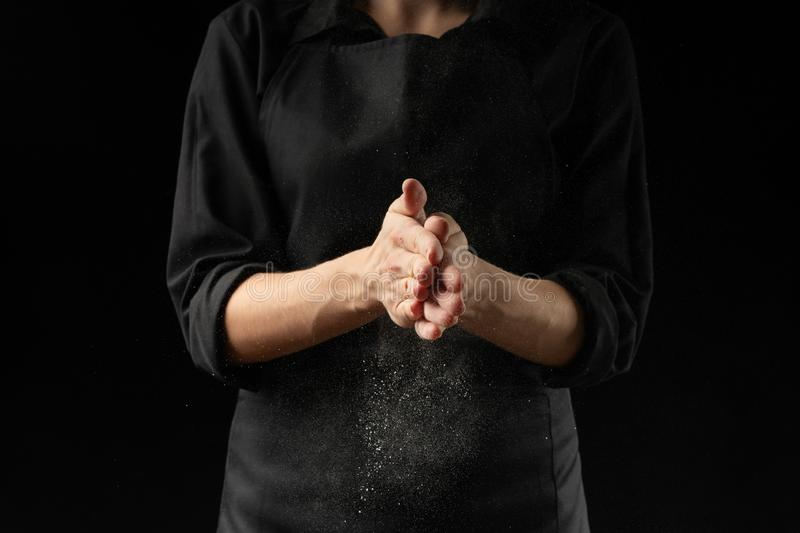 Baker, chef making cotton with flour, freezing flour in the air. Banner, on a black background. Splash of flour. Cooking bread, royalty free stock photo