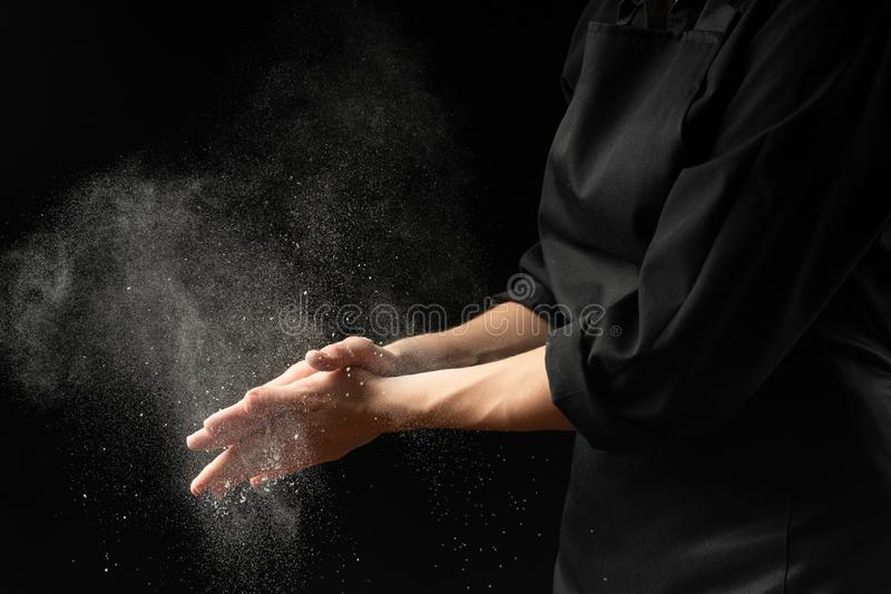 Baker, chef making cotton with flour, freezing flour in the air. Banner, on a black background. Splash of flour. Cooking bread, stock photo