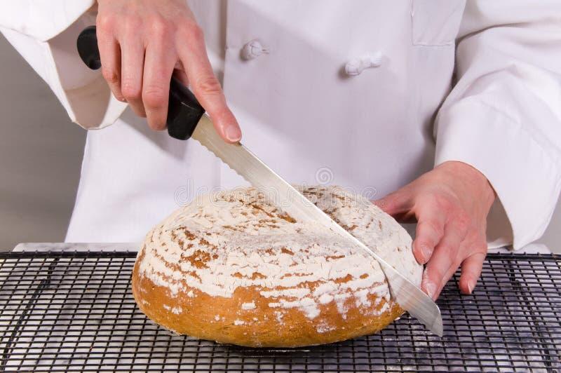 Baker découpe en tranches autour du pain images stock