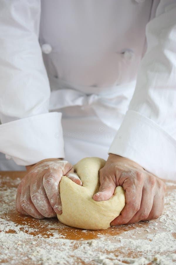 Baker dat brood maakt, dat een deeg kneedt stock fotografie