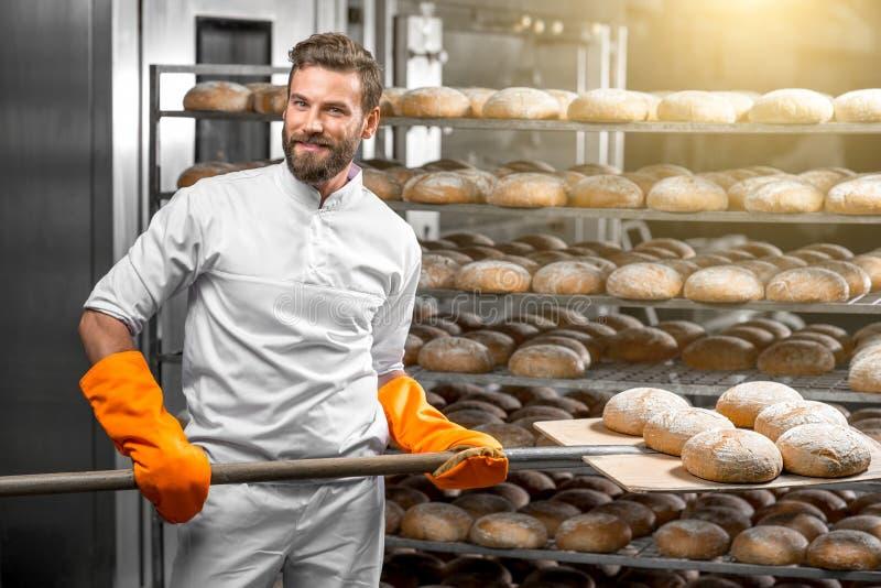 Baker die met de broden van het schopbrood bij de productie zetten royalty-vrije stock afbeelding