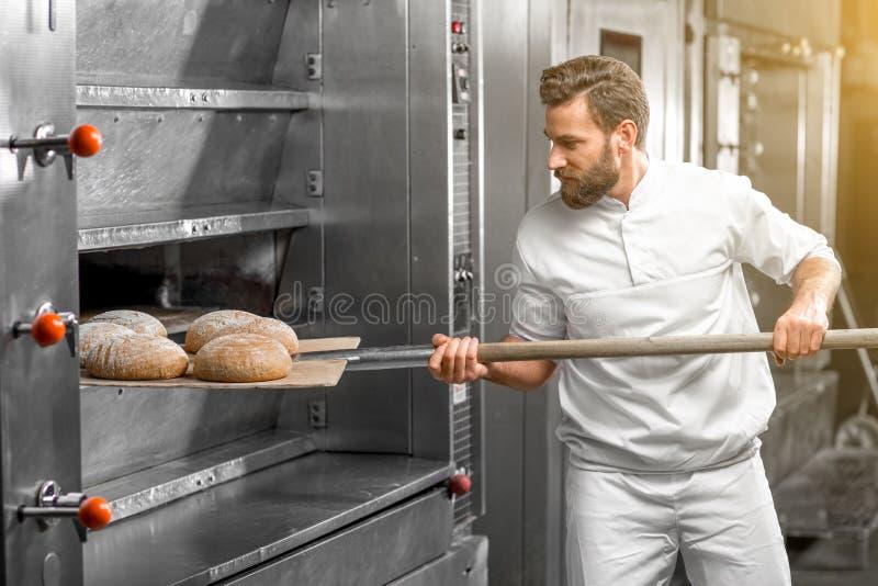 Baker die uit het oven gebakken buckweat brood nemen royalty-vrije stock fotografie