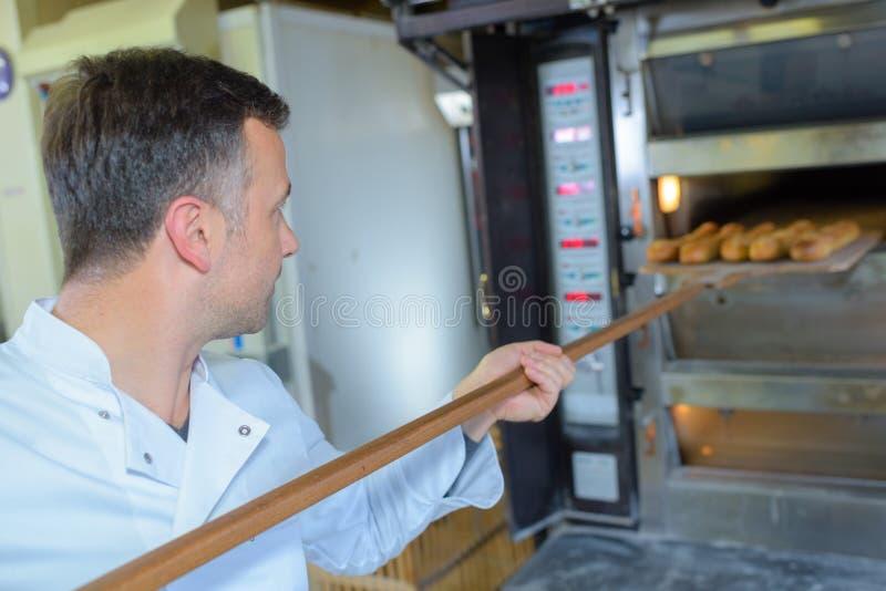 Baker die verse brood uit traditionele oven krijgen stock foto