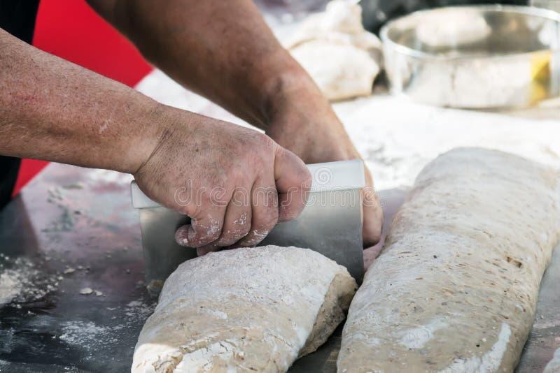 Baker divise la pâte en parties pour le pain de cuisson image libre de droits