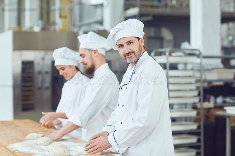 Baker with dough in hand in the bakery. Baker with dough in hand against the background of workers in the bakery. A team of bakers works in the workplace at the royalty free stock photo