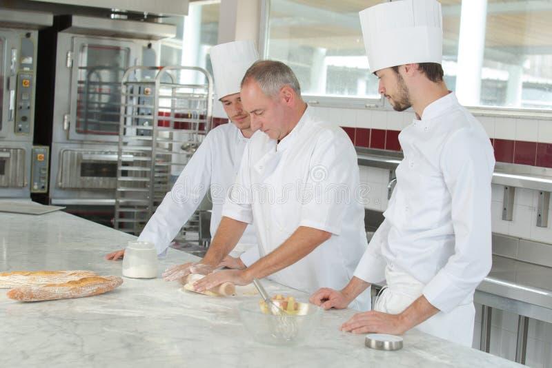 Baker en medewerkers in bakkerijkeuken stock foto
