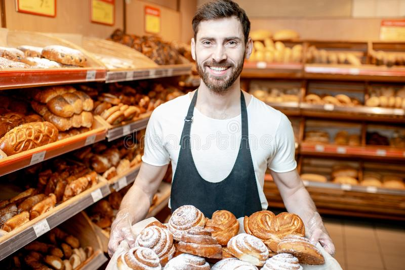 Baker with fresh pastries in the supermarket. Portrait of a handsome baker in uniform standing with fresh pastries in the bakery deparment of the supermarket stock photography