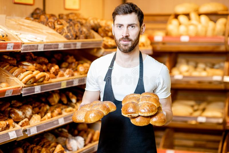 Baker with fresh pastries in the supermarket. Portrait of a handsome baker in uniform standing with fresh pastries in the bakery deparment of the supermarket stock photos