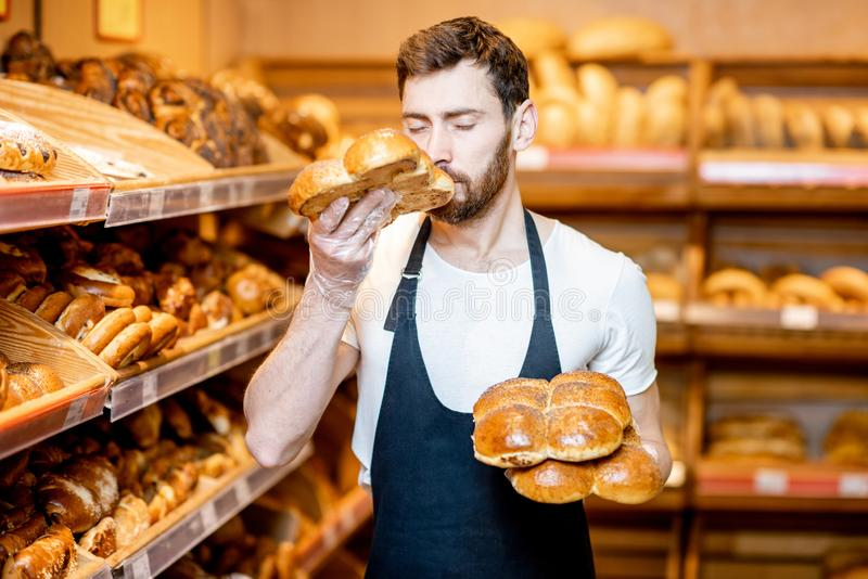 Baker with fresh pastries in the supermarket. Portrait of a handsome baker in uniform standing with fresh pastries in the bakery deparment of the supermarket stock images