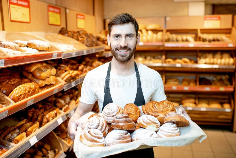Baker with fresh pastries in the supermarket. Portrait of a handsome baker in uniform standing with fresh pastries in the bakery deparment of the supermarket royalty free stock photos