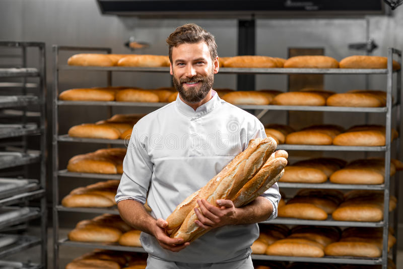 Baker holding baguettes at the manufacturing royalty free stock photo
