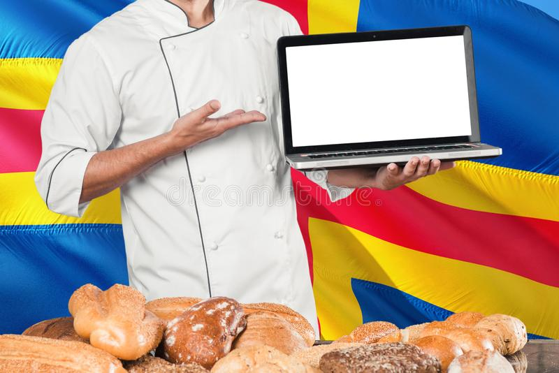 Baker holding laptop on Aland Islands flag and breads background. Chef wearing uniform pointing blank screen for copy space.  stock images