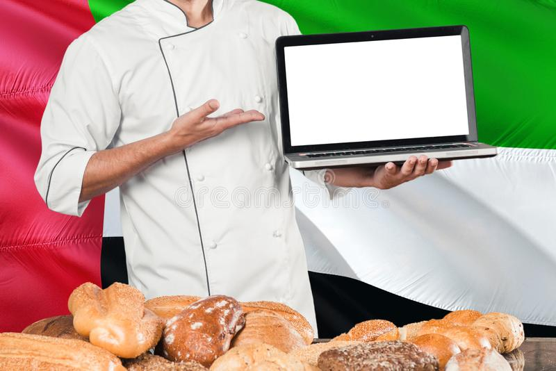Baker holding laptop on United Arab Emirates flag and breads background. Chef wearing uniform pointing blank screen for copy space royalty free stock images