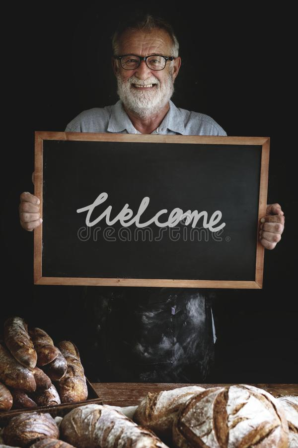 Baker holding a welcome sign stock images