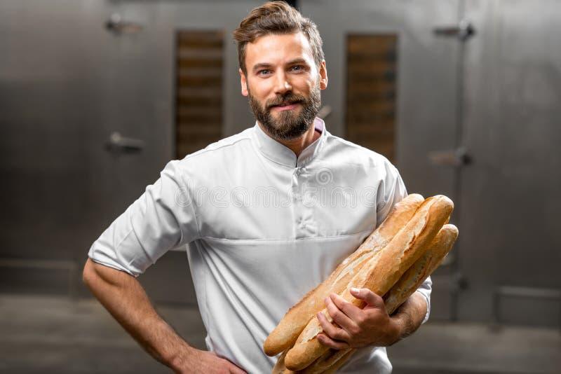 Baker holdingsbaguettes bij de productie royalty-vrije stock fotografie