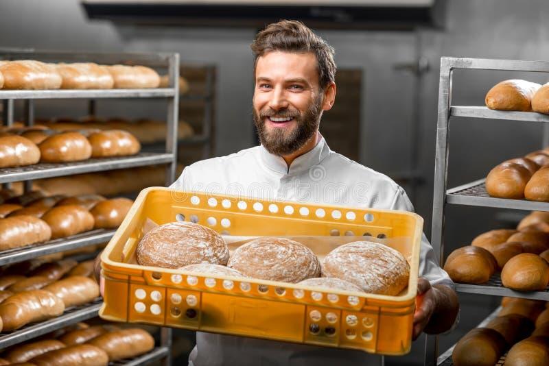 Baker holdingsbroden bij de productie stock afbeelding