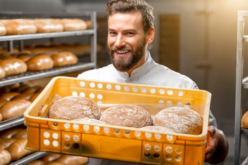 Baker holdingsbroden bij de productie royalty-vrije stock afbeelding