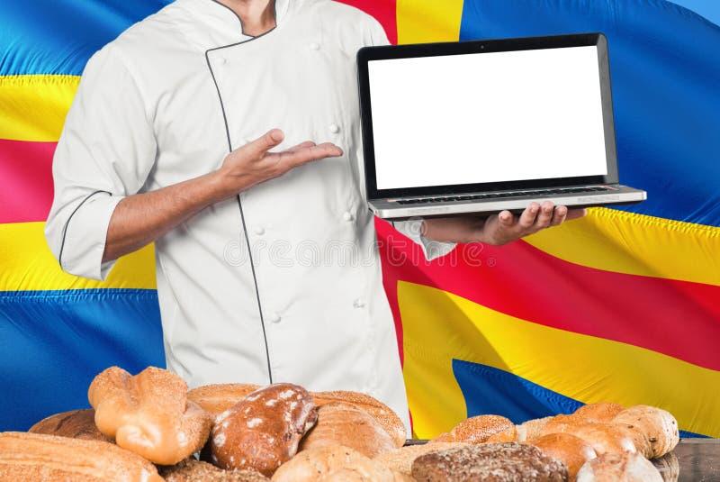 Baker holdingslaptop op Aland-Eilandenvlag en brodenachtergrond Chef-kok die het eenvormige het richten lege scherm voor exemplaa stock afbeeldingen