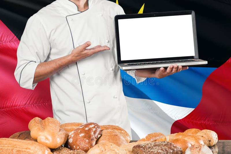 Baker holdingslaptop op Antigua en van Barbuda vlag en brodenachtergrond Chef-kok die het eenvormige het richten lege scherm voor stock foto's