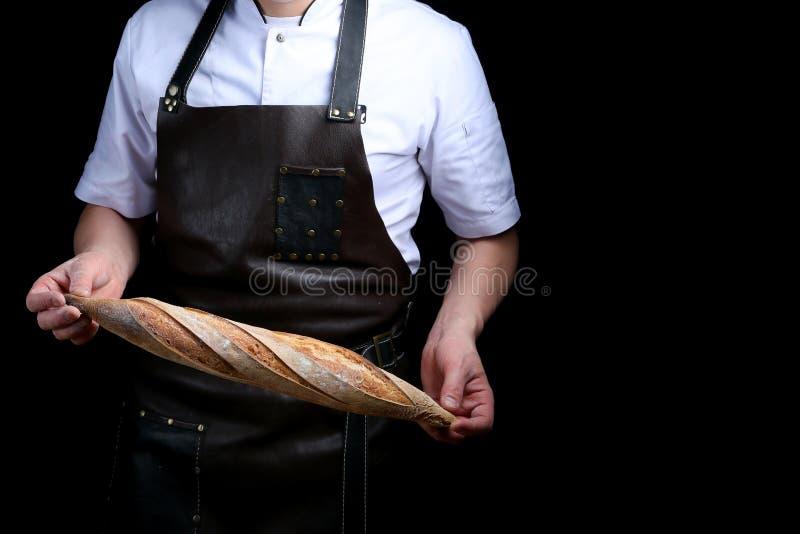 Baker holds baguette isolated on black background stock images