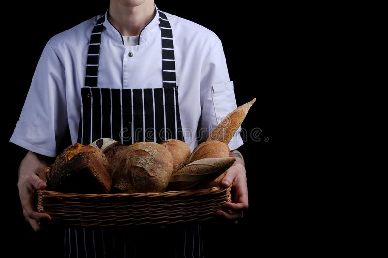Baker holds basket of bread on black background isolated royalty free stock images