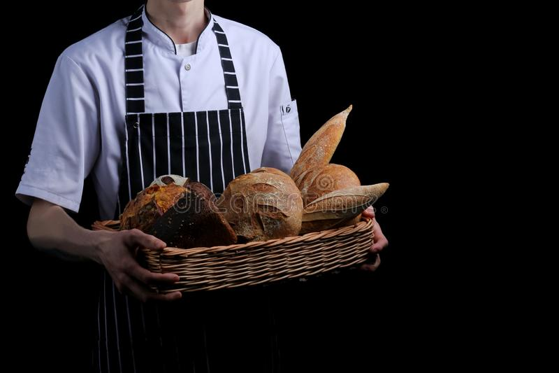Baker holds basket of bread isolated on black background stock photography