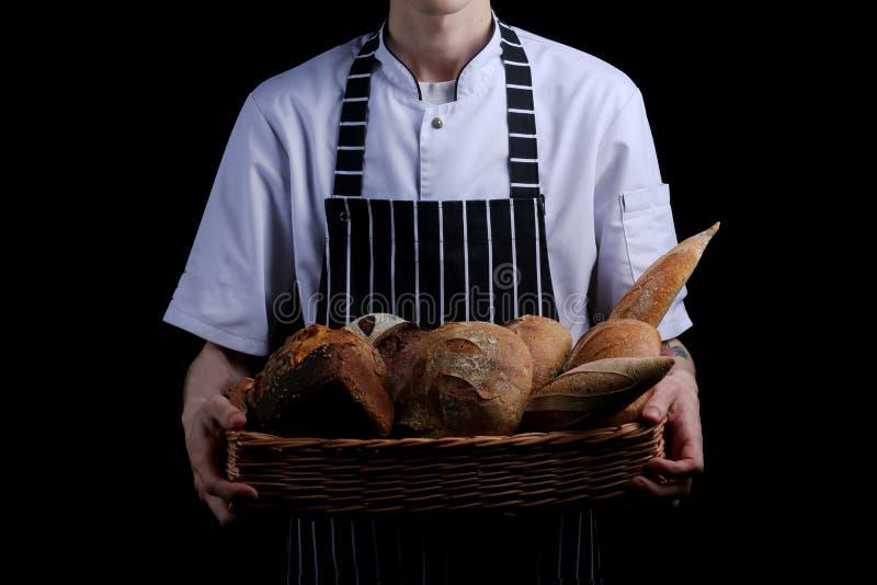 baker holds basket of bread isolated on black background stock photo