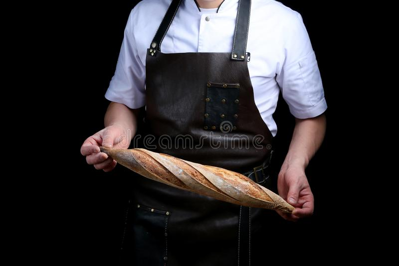 Baker houdt baguette op zwarte achtergrond wordt geïsoleerd die royalty-vrije stock foto's
