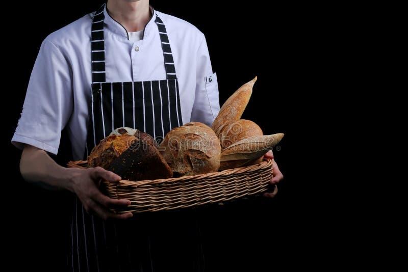 Baker houdt mand brood op zwarte achtergrond wordt geïsoleerd die stock fotografie