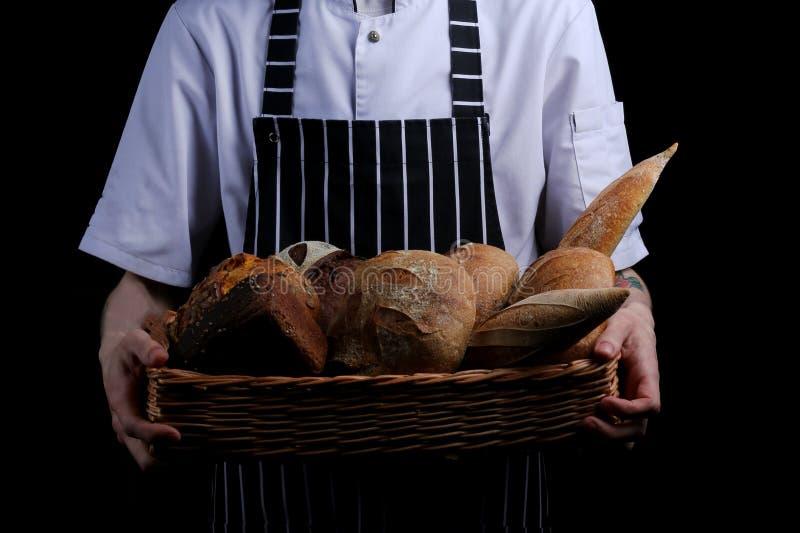 Baker houdt mand brood op zwarte achtergrond wordt geïsoleerd die royalty-vrije stock foto's