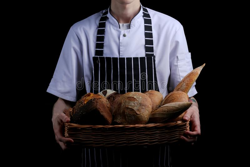 Baker houdt mand brood op zwarte achtergrond wordt geïsoleerd die stock foto