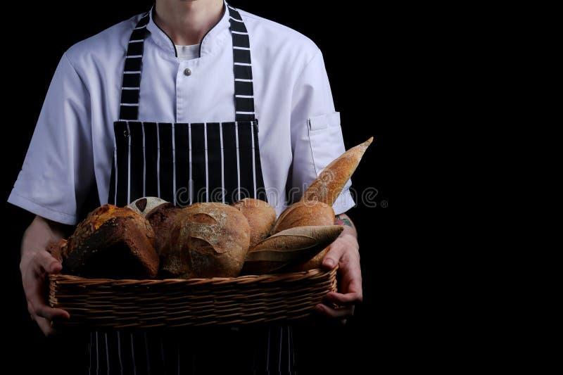 Baker houdt mand brood op zwarte geïsoleerde achtergrond stock afbeeldingen