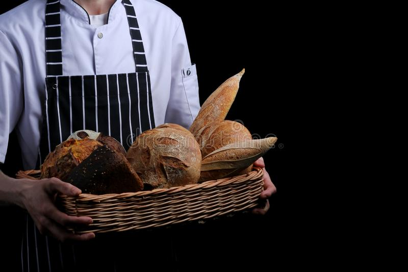 Baker houdt mand brood op zwarte geïsoleerde achtergrond royalty-vrije stock foto